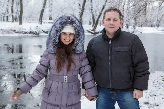 A man and woman are standing near river in snowy park on winter day