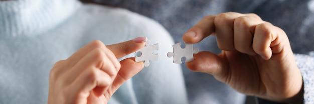 Man and woman are trying to connect white puzzles together