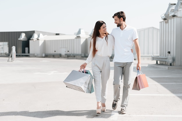 Man and woman are walking on parking after shopping.