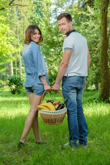 Man and woman are walking on picnic in park.
