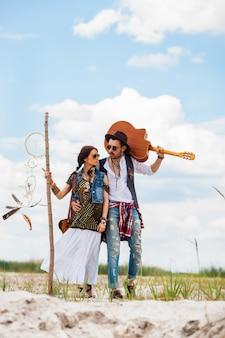 Uomo e donna come pantaloni a vita bassa di boho contro cielo blu
