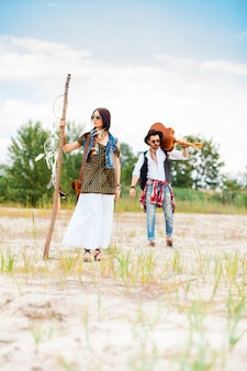 Man and woman as boho hipsters against blue sky