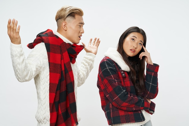 Man and woman of asian appearance with checkered scarf and jacket