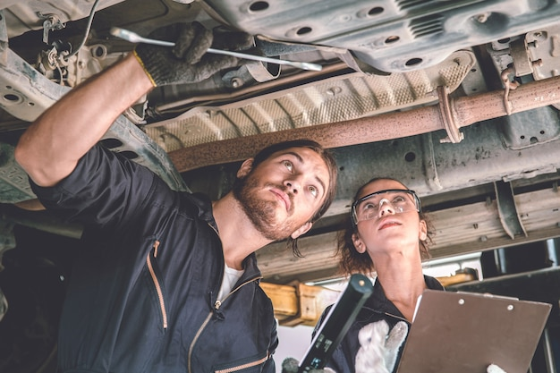 Man and woman auto mechanic working team checking under car for auto maintenance and service in garage