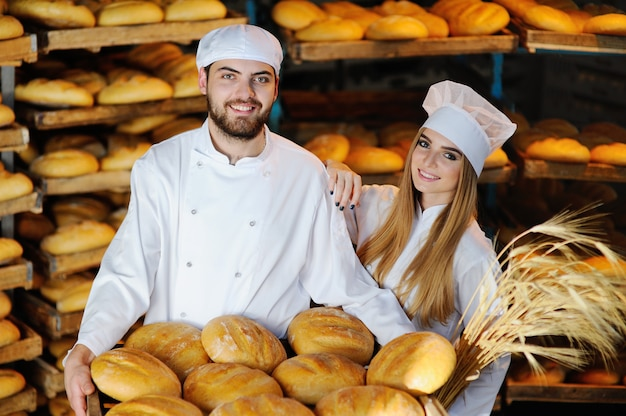 Man and woman on background bread bakers