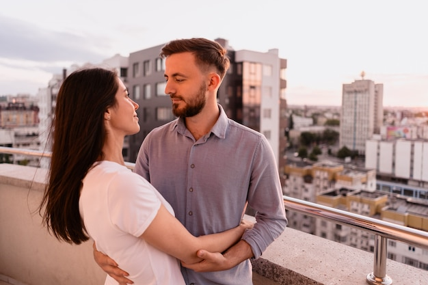 Man and woman on balcony at sunset in the city