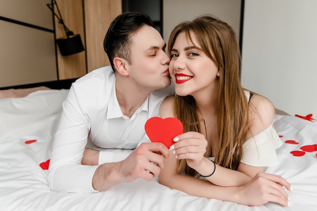 Man and woman in bed with heart shape in hands
