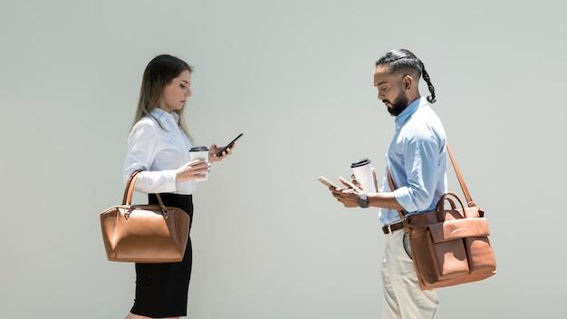 L'uomo e la donna sono dipendenti dai loro telefoni anche all'aperto