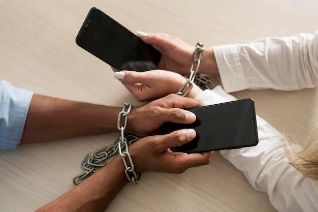 L'uomo e la donna sono dipendenti dai loro telefoni anche al lavoro
