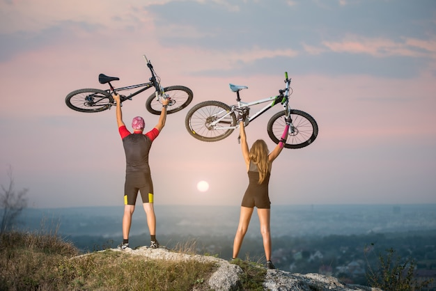 Man and woman bikers holding bikes high up