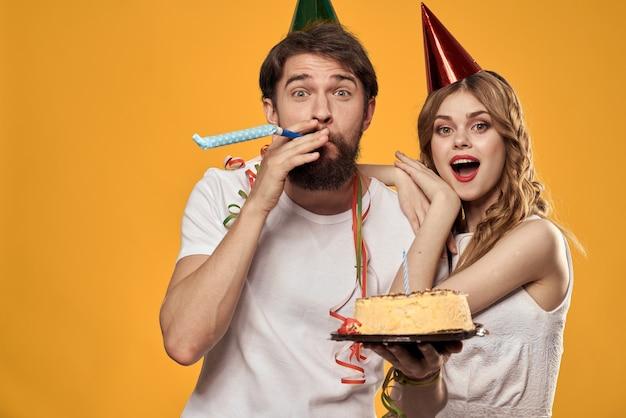 Man and woman birthday festive cake yellow background