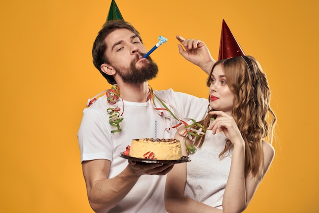 A man and a woman on a birthday with a cupcake and a candle in a festive cap have fun and celebrate the holiday together, happy couple