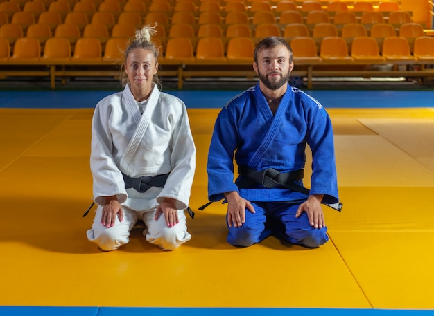 Man and woman in blue and white kimono with black belt sit on the floor and meditate in the sports hall. oriental martial arts, judo