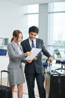 Man and woman in business suits standing in office with suitcases and looking together at document