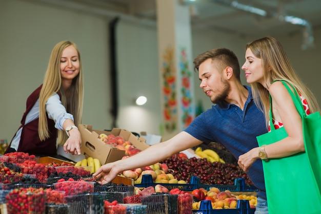 Man and woman buy berries at market