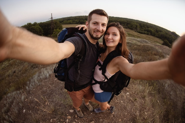 A man and a woman on a camping trip take a selfie near the tent.