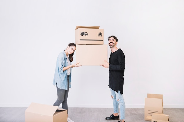 Man and woman carrying moving boxes