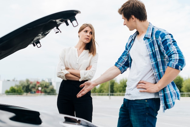Man and woman checking car engine