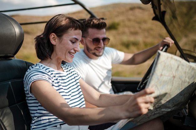 Man and woman checking map while traveling by car