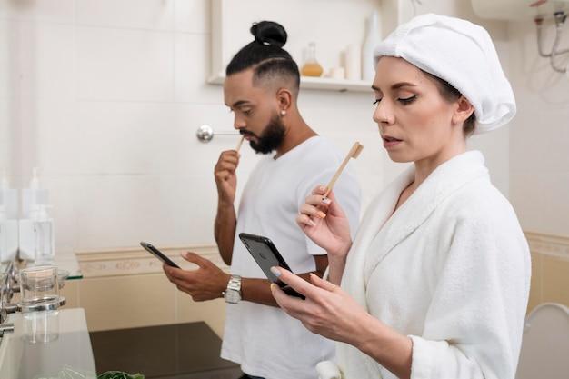 Uomo e donna che controllano i loro telefoni anche nel loro bagno