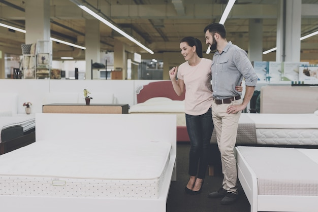 A man and a woman choose a bed in the store.