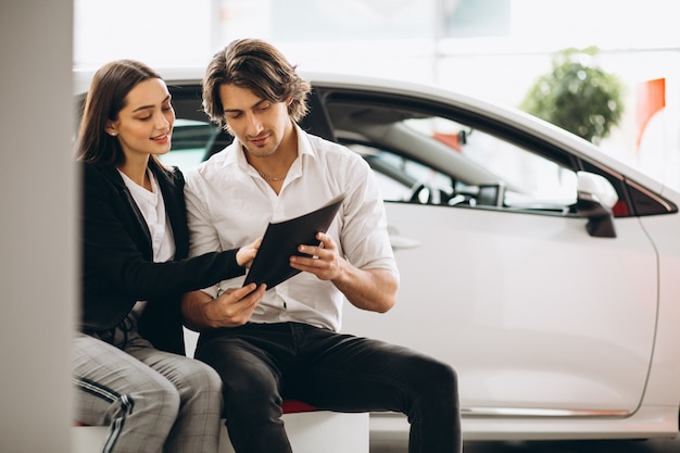 Man and woman choosing a car in a car showroom