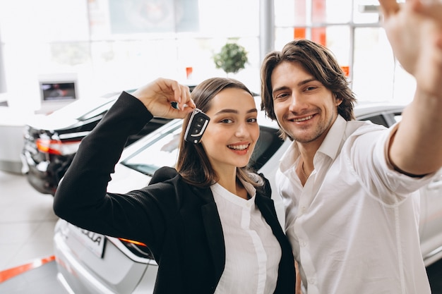 Man and woman choosing a car in a car showroom