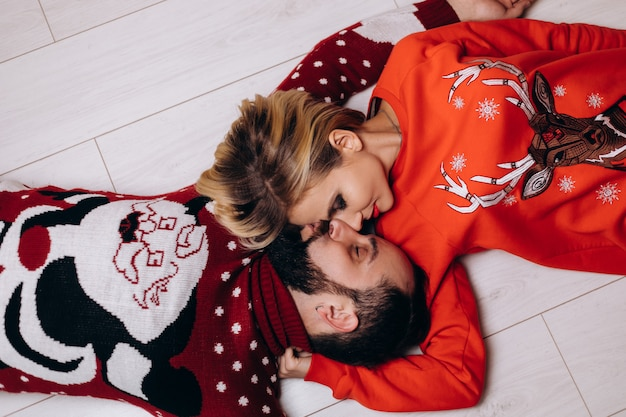 Man and woman in christmas sweaters hug each other tender lying on the floor