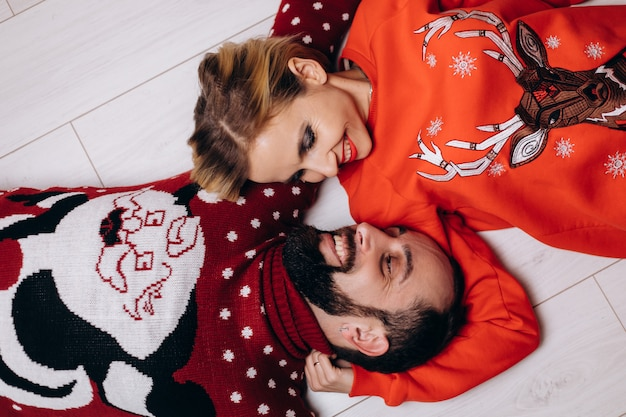 Man and woman in christmas sweaters hug each other tender lying