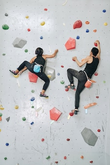 Man and woman clambering wall in gym