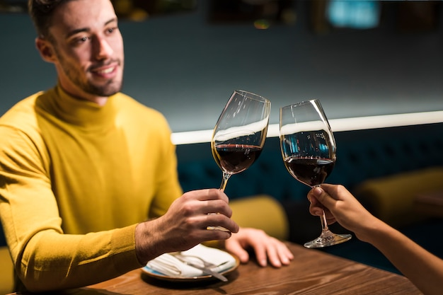 Man and woman clanging glasses of wine at table in restaurant