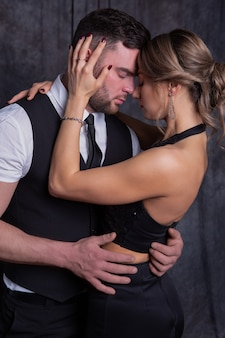 Man and a woman closing their eyes with pleasure tenderly embrace each other