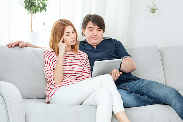 Man and woman communicate by video link. chatting online and waving at the computer screen.