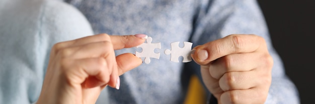 Man and woman connect white puzzles closeup