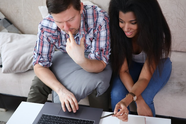 Man and woman on couch and looking at laptop
