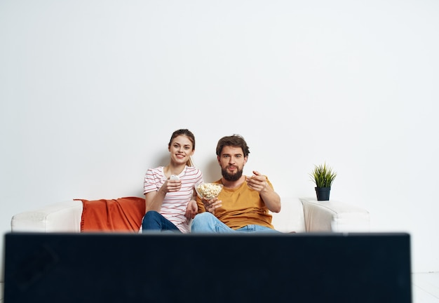 A man and a woman on the couch watching the tv indoors watching the show