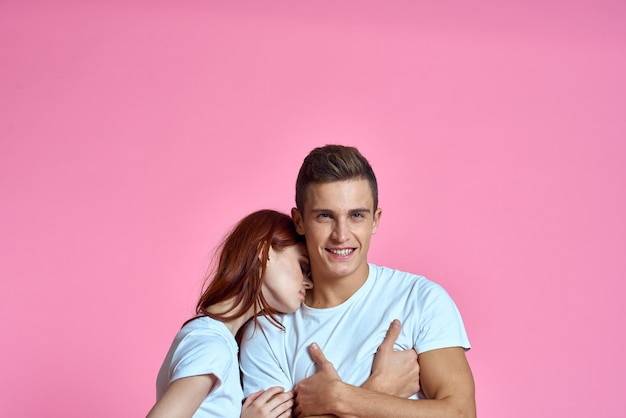 Man and woman couple posing in white t-shirts.