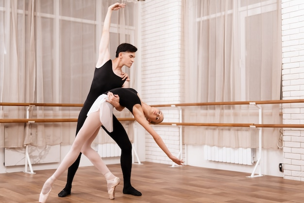 Man and woman dancers posing in ballet class.
