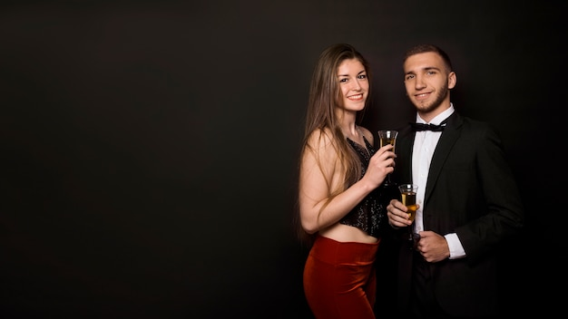Man and woman in dinner jacket and evening wear with glasses of drinks