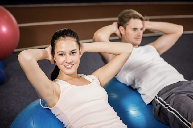 Man and woman doing abdominal crunches on fitness ball