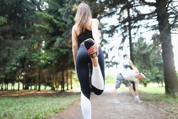 Man and woman doing sports exercises in park.