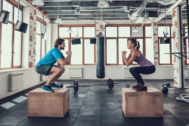 Man and woman doing squats on wood blocks in gym.