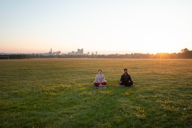 Uomo e donna che fanno yoga insieme all'aperto