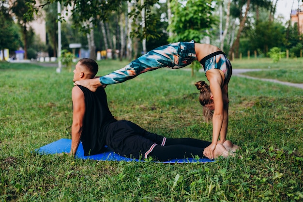 Man and woman doing yoga together in the park outdoor. man kissing a woman