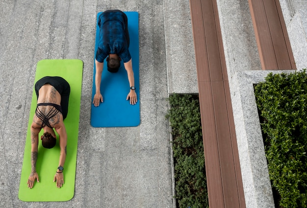 Man and woman doing yoga training on mats