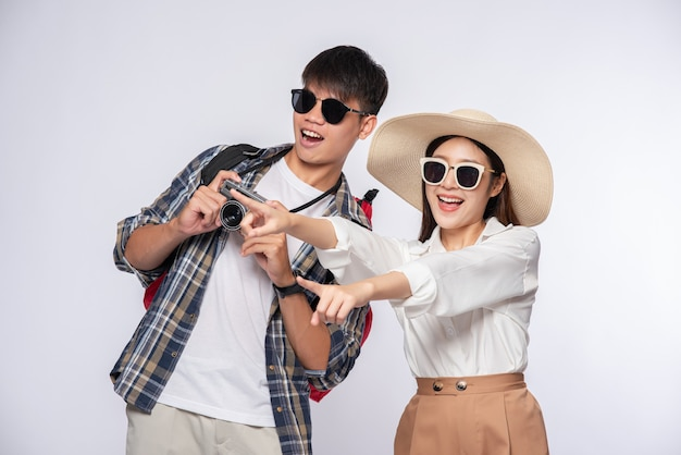 Man and woman dressed to travel, wear glasses, and take pictures
