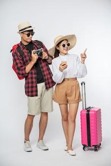 Uomo e donna vestiti per viaggiare, indossare occhiali e scattare foto