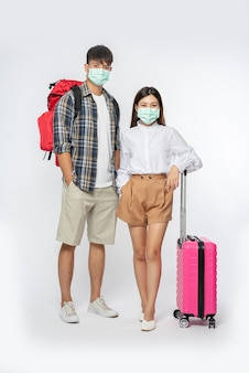 Man and woman dressed to travel, wearing masks along with luggage