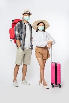 Uomo e donna vestiti per viaggiare, che indossano maschere insieme ai bagagli