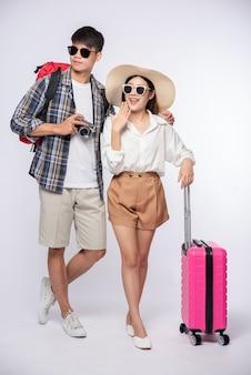 Uomo e donna vestiti con gli occhiali per viaggiare con le valigie